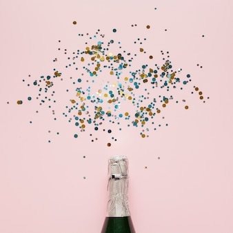 Arrangement of champagne bottle and colourful confetti
