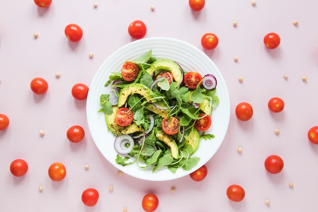 Arrangement of cherry tomatoes with bowl of salad