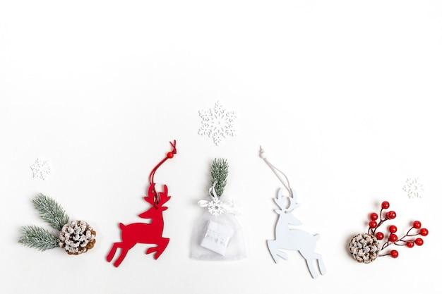 Arrangement of christmas decorations deer, fir twigs, red berries, snowflakes and diy gift on white backdrop