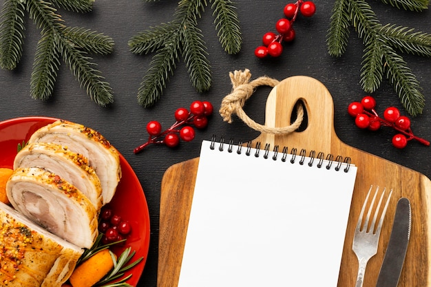 Disposizione del cibo natalizio con blocco note vuoto