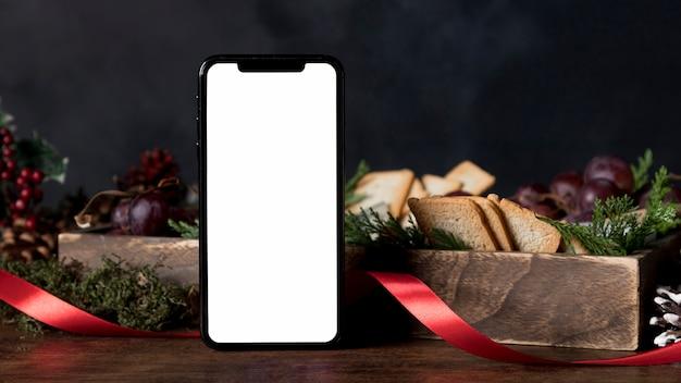 Disposizione del cibo natalizio con smartphone vuoto