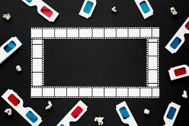 Arrangement of cinema elements on black background with film frame