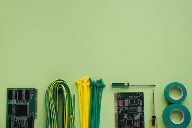 Arrangement of circuit board; wire; nylon zip wire; tester and insulating tape over green backdrop