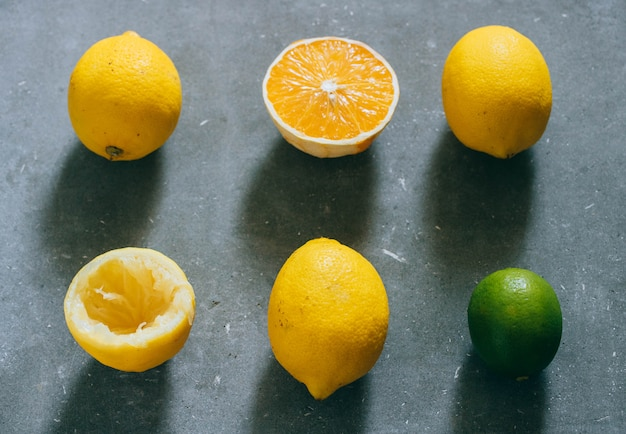 An arrangement of citrus fruits, lemons, orange and limes on a gray background.