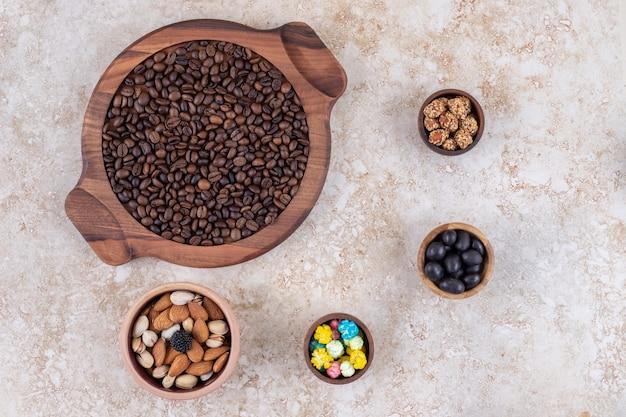 Una disposizione di chicchi di caffè, arachidi glassate, caramelle e noci assortite