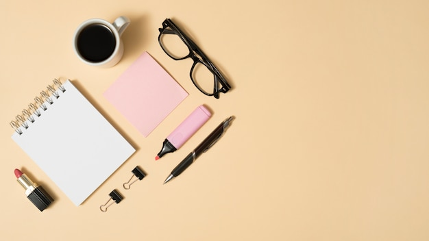 Arrangement of coffee cup; eyeglass; lipstick; with office stuff on beige backdrop