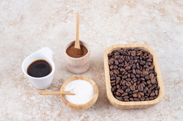 An arrangement of coffee cup, sugar, ground coffee powder and a pile of coffee beans in a wooden platter