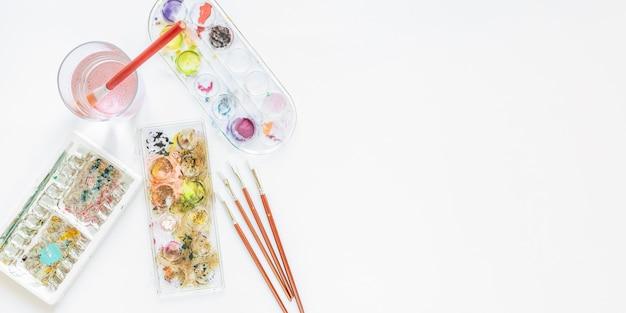 Disposizione della tavolozza dei colori in scatola e pennelli
