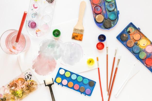 Disposizione della tavolozza dei colori in scatole e pennelli