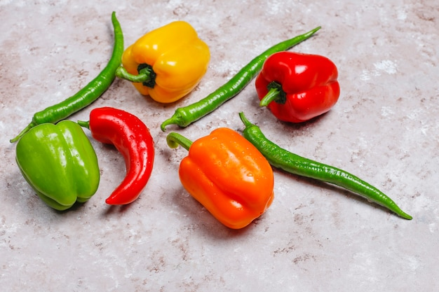 Arrangement of colorful fresh assorted bell pepperson concrete surface