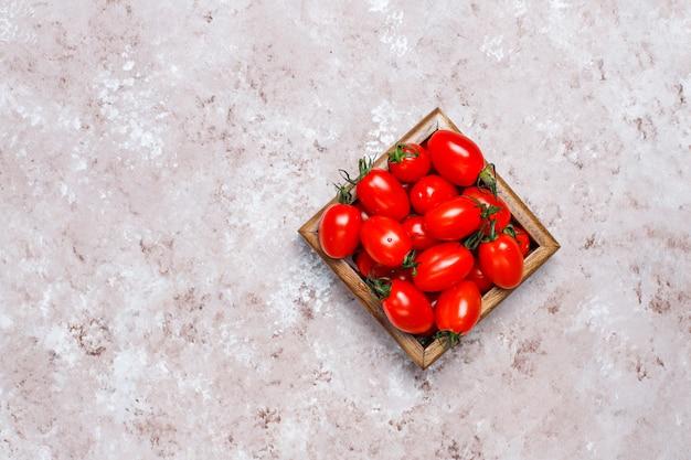 Disposizione dei pomodori assortiti freschi colorati sulla superficie del calcestruzzo