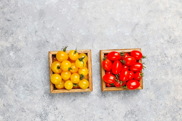 Arrangement of colorful fresh assorted tomatoes on concrete surface