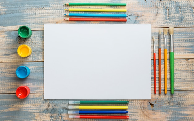 Arrangement of colorful painting equipment and blank sheet on wooden backdrop