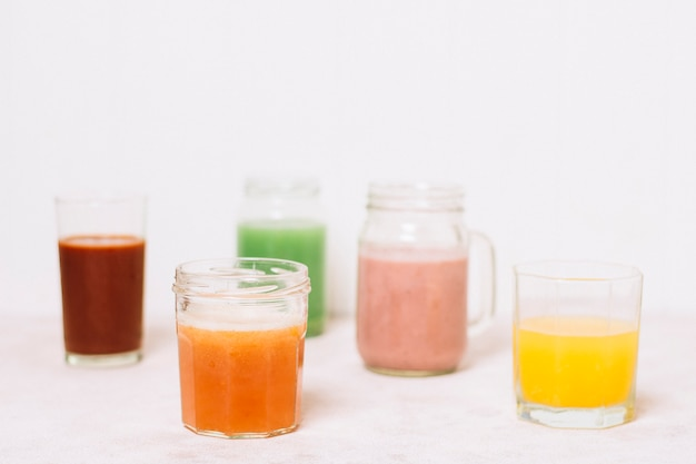 Arrangement of colorful smoothies with white background