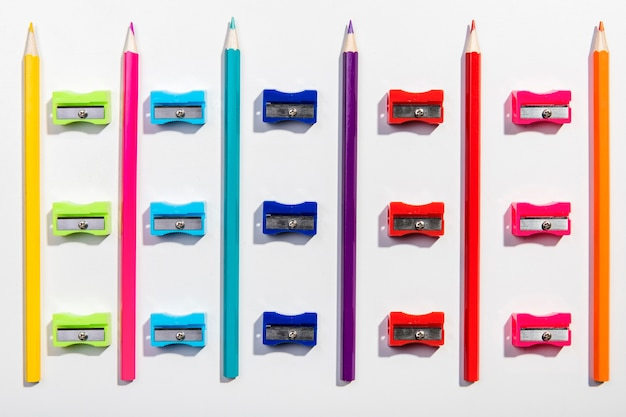 Arrangement of colourful pencils and sharpeners top view
