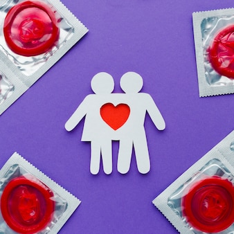 Arrangement of contraception concept with red condoms and paper couple