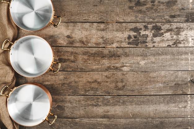 Arrangement of copper cooking pots on old grunge wooden background
