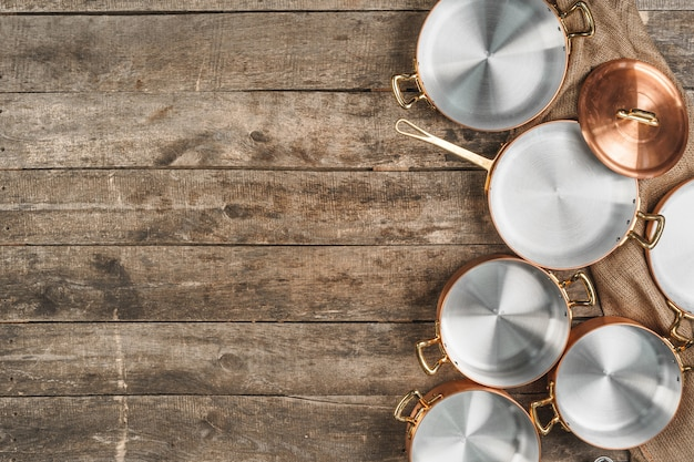 Arrangement of copper cooking pots on old grunge wooden