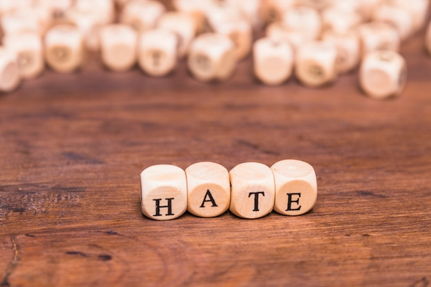 Arrangement of cubes with text hate on wooden table