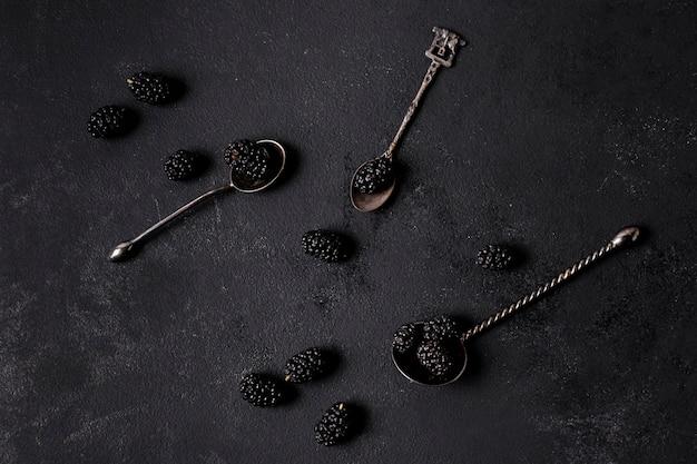 Arrangement of delicious blackberries in spoons