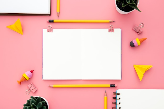 Arrangement of desk elements on pink background with empty notebook