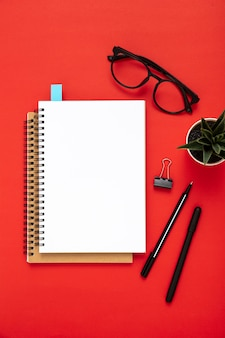 Arrangement of desk elements with empty notebook on red background