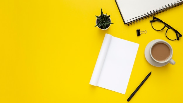Arrangement of desk elements with empty notepad on yellow background