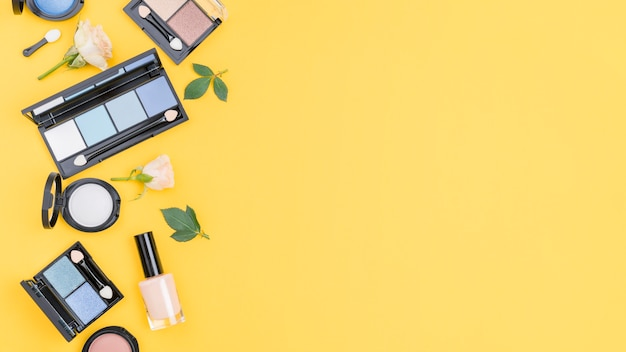 Arrangement of different cosmetics with copy space on yellow background