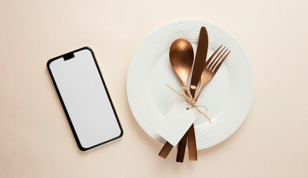 Arrangement of elegant tableware with empty smartphone