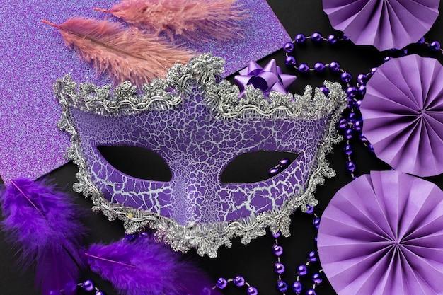 Arrangement of elegant violet mask and decoration