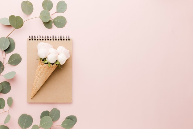 Arrangement of floral ice cream cone and notebook