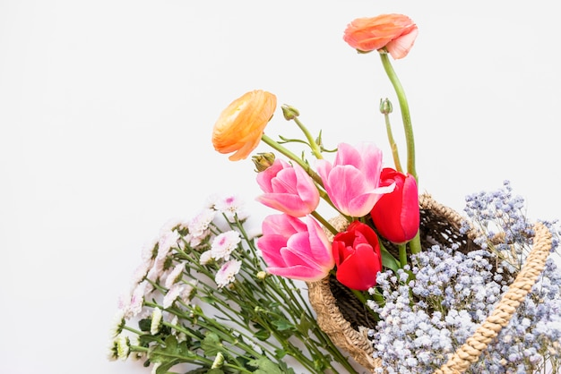 Arrangement of flowers in basket on white background