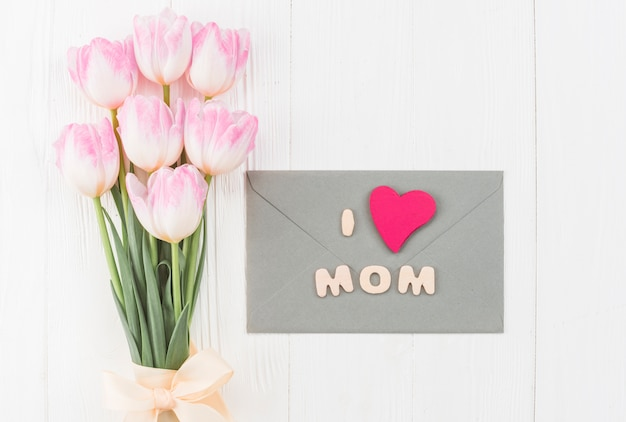 Arrangement of flowers and envelope for mothers`s day