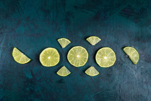 Arrangement of fresh juicy ime slices on emerald background. lime is ingredient for mojito.