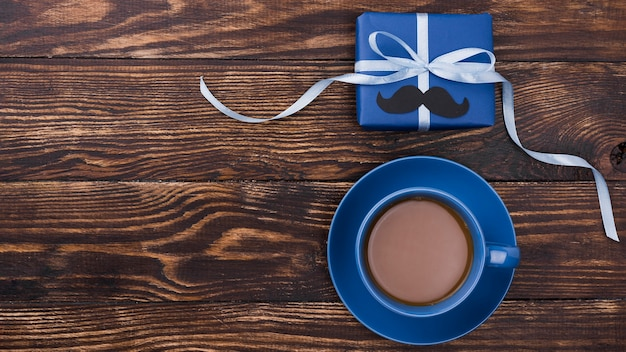 Arrangement of gift with ribbon and coffee