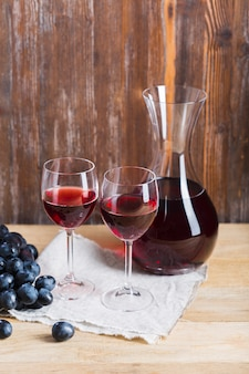 Arrangement of glasses and carafe of wine on wooden background