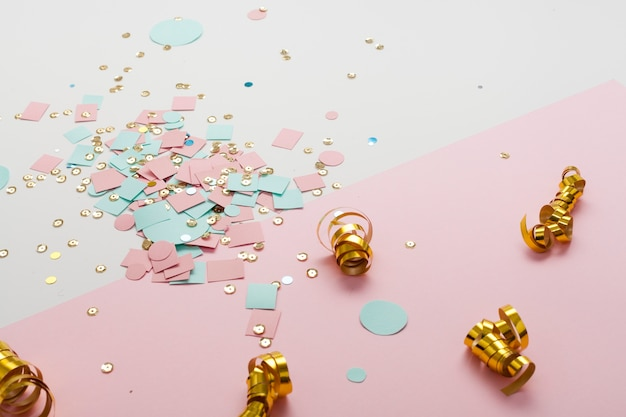 Arrangement of golden confetti and colourful paper