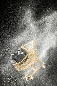 Arrangement of golden shopping cart with white glitter