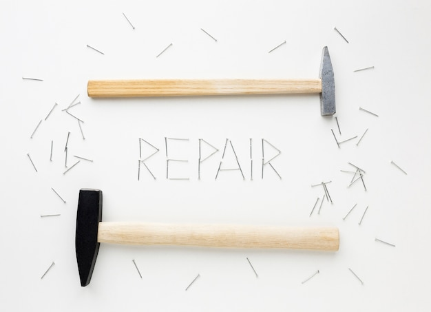 Arrangement of hammers and repair word written with nails