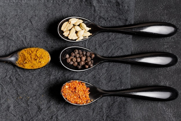 Arrangement of healthy spices in spoons flat lay