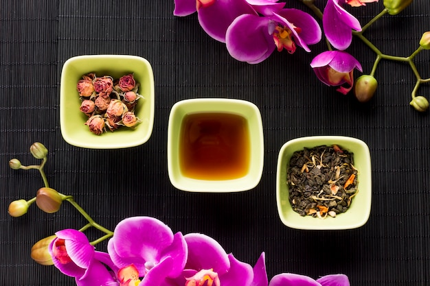 Arrangement of herbal tea and pink orchid flower over black place mat