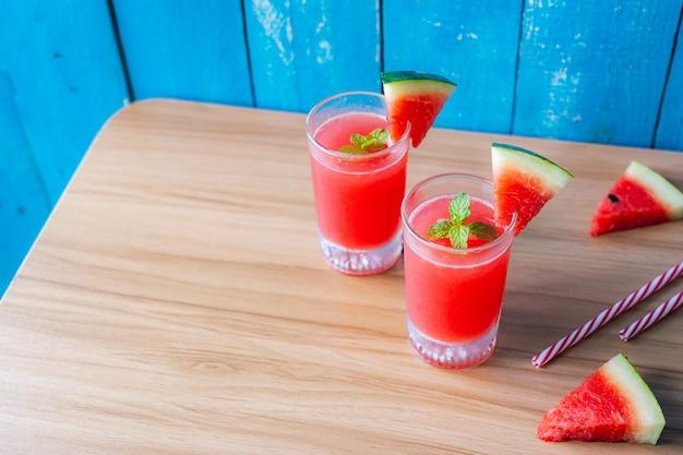 Arrangement items sliced watermelon juice on modern brown blue wooden.