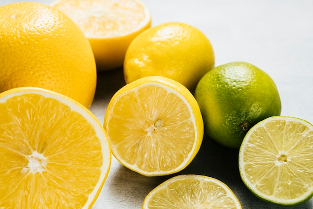 Arrangement of lemons and limes on plain background