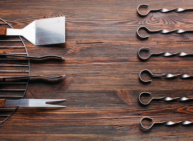 Arrangement of new barbecue utensil set over wooden surface