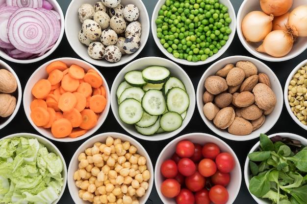 Расположение мисок, наполненных овощами и фруктами