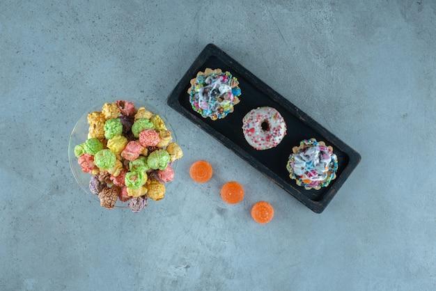 대리석 표면에 도넛, 팝콘, 컵 케이크 및 젤리 캔디와 함께 설탕에 절인 스낵 배열