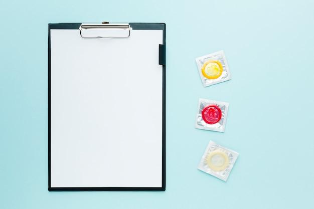 空のクリップボードと青色の背景に避妊の概念の配置