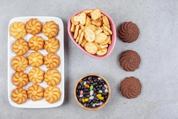Расположение печенья на блюде и вне тарелки с мисками крекеров и конфет посередине на мраморном фоне. фото высокого качества