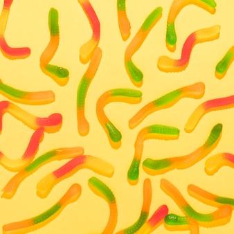 黄色の背景に異なる色のキャンディーの配置