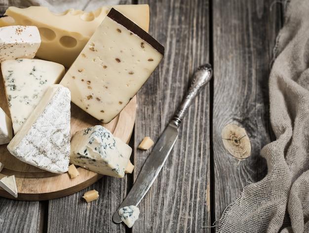 Расположение изысканных сыров на деревянных фоне, концепция изысканных сыров